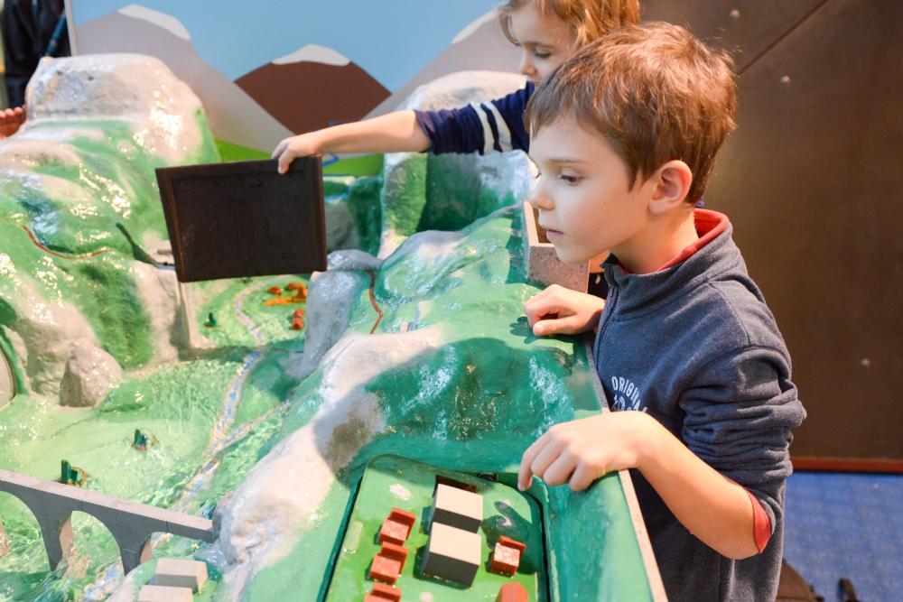 Deux enfants jouant avec une grande maquette de paysage.