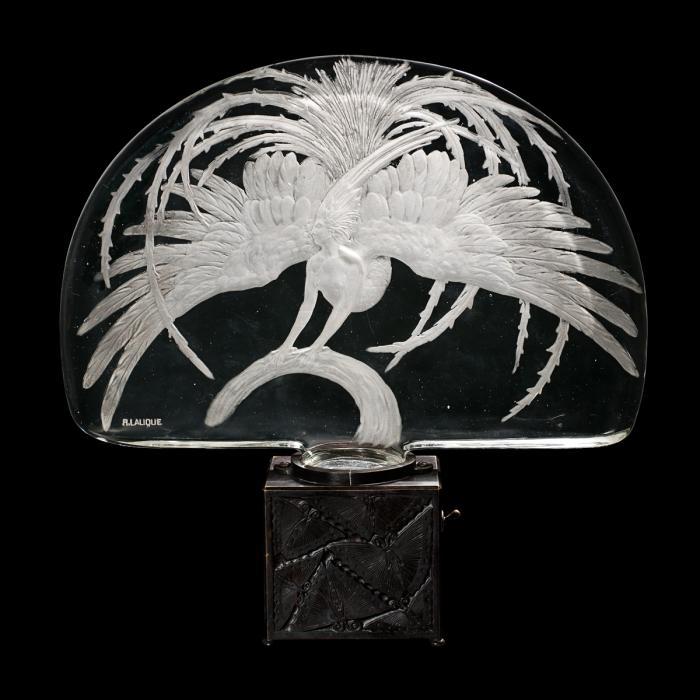 Élément décoratif avec une base en métal cubique surmontée d'un panneau demi-circulaire en verre représentant une femme hybride avec de grandes ailes et une queue d'oiseau de feu.