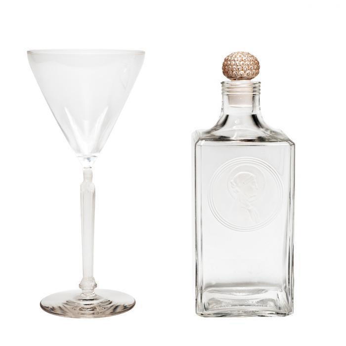 Un verre et une petite carafe carrée incolores - Sainte Odile est présente sur la jambe du verre comme une statuette et dans un médaillon rond en portrait sur la carafe