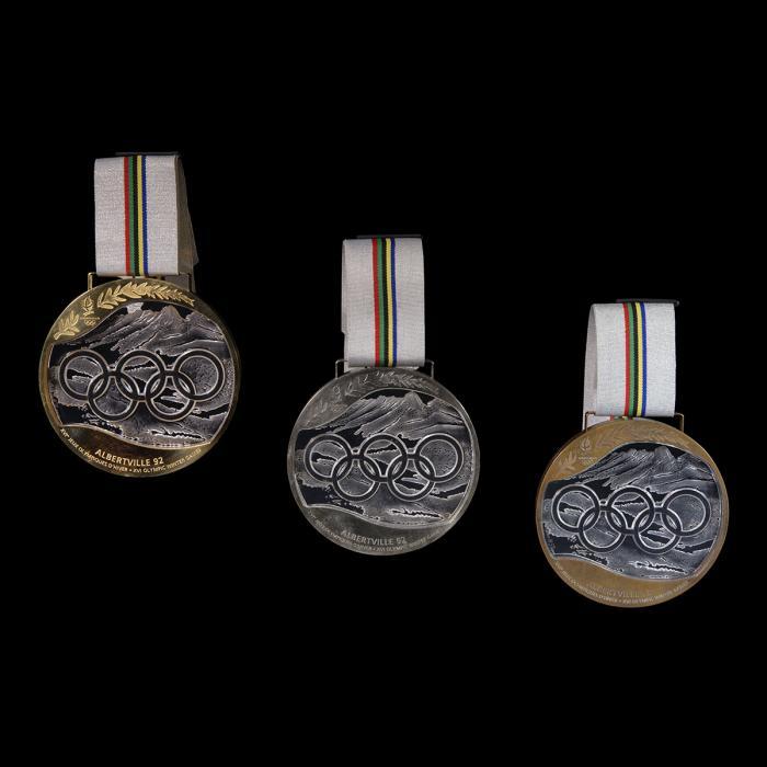 Ces trois médailles sont constituées d'une partie centrale en cristal représentant les cinq anneaux entrecroisés des Jeux Olympiques sur fond de montagnes savoyardes. Autour, un cercle de métal précieux (or, argent ou bronze) gravé d'une palme, symbole de victoire, en haut ainsi que de la mention
