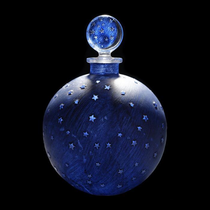 Flacon de parfum en verre, de couleur bleu nuit avec des petites étoiles incolores. Bouchon rond décor bleu avec des étoiles transparentes