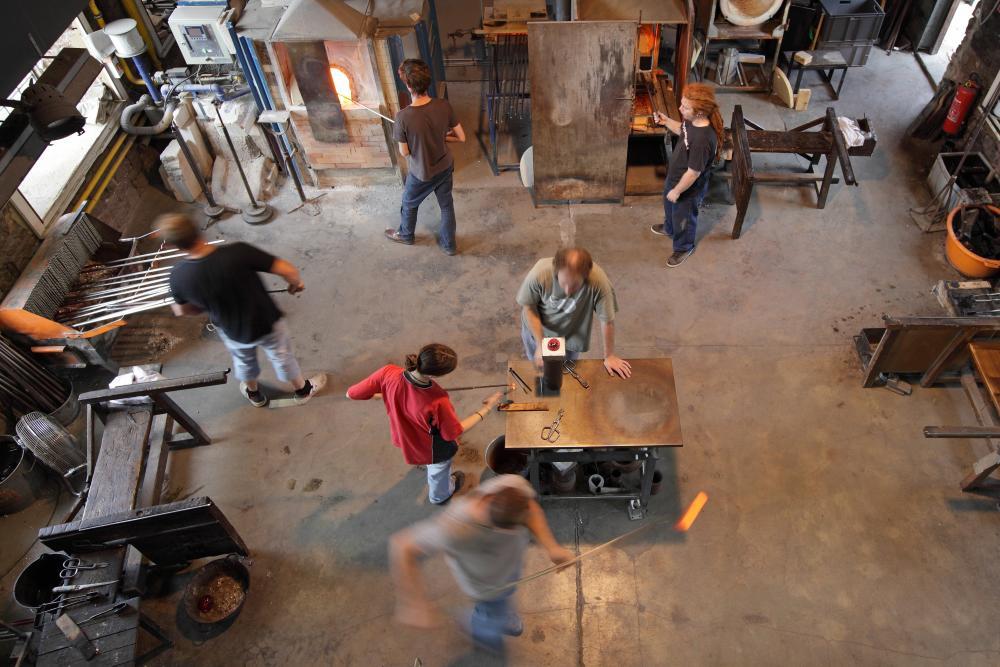 Vue en plongé de six hommes au travail dans l'atelier verrier de Meisenthal. L'un, à gauche, saisie une cane en métal; un autre, en haut, cueille du verre en fusion dans le four; le suivant tient une cane plongée dans un four; et plus bas, autour d'une table de travail, une femme et deux hommes travaillent sur une pièce en verre rouge.