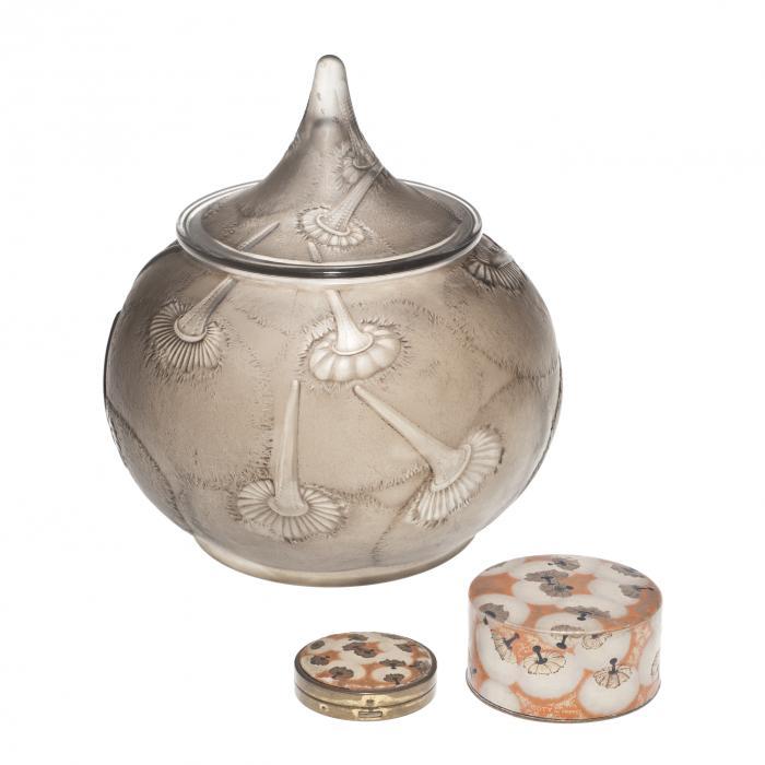 Au fond, un vase en verre en forme de goutte d'eau avec des motifs de houppes. Au premier plan à droite, une petite boite ronde de couleur orange avec des motifs de houppe. Au premier plan à gauche, un poudrier assorti à la boite.