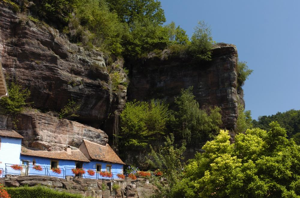Photographie d'une partie des maisons troglodytiques à flanc de rochers en grès rose.