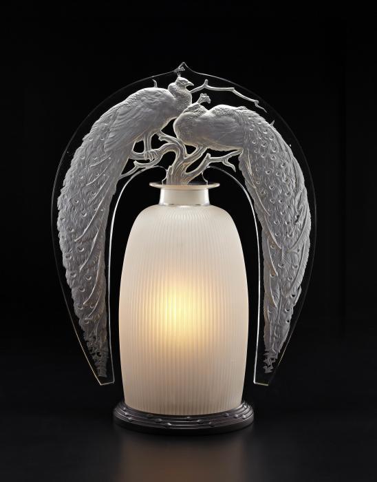 Veilleuse délicate ressemblant à un flacon de parfum dont le corps, strié sur la longueur, est opalescent. Sur le sommet de la pièce repose une tranche en verre montrant deux paons à longues queues posés sur les branches d'un arbre.