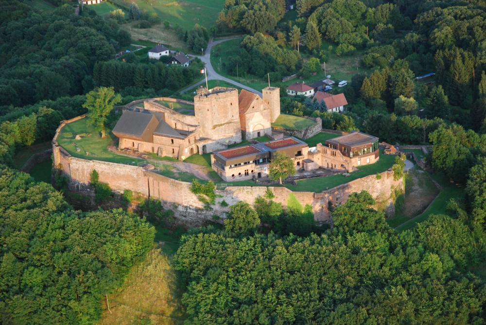 Photographie aérienne du Château du Lichtenberg avec ses remparts entourés d'une forêt luxuriante.