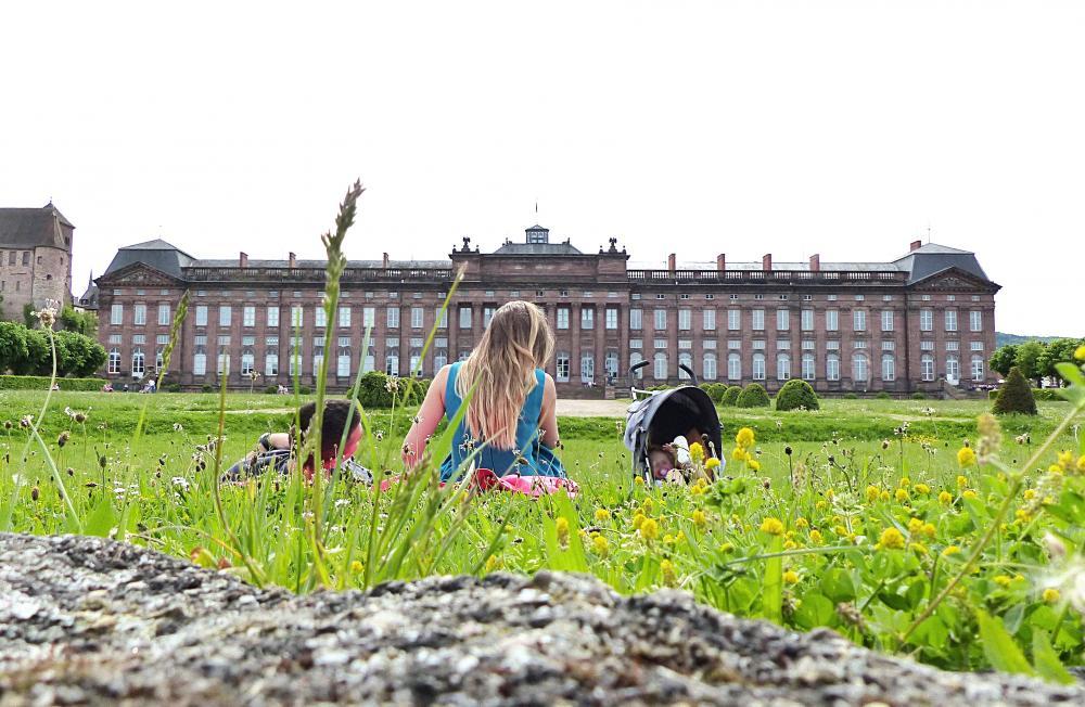 Vue d'un jeune couple, au premier plan, se reposant dans le jardin du Château des Rohan, à l'arrière plan.