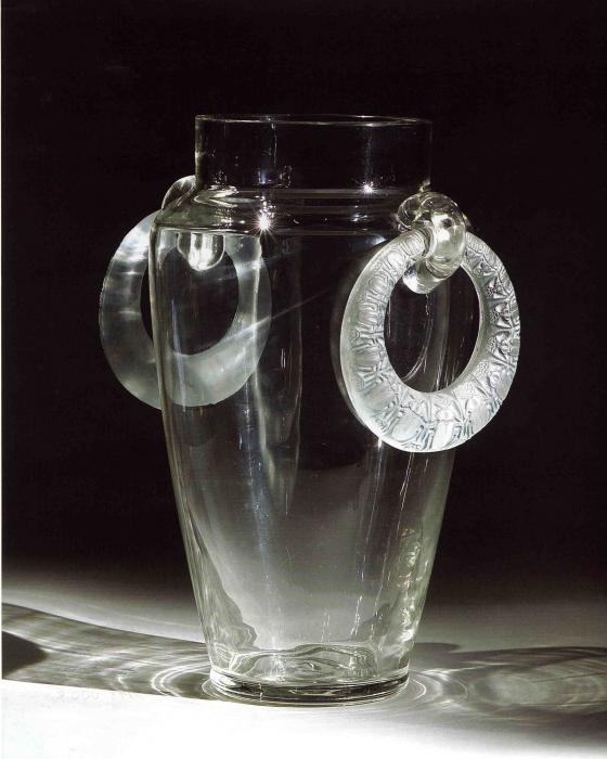 Vase en verre dont les anses forment deux grosses boucles avec des motifs de scarabées vus de dessus.