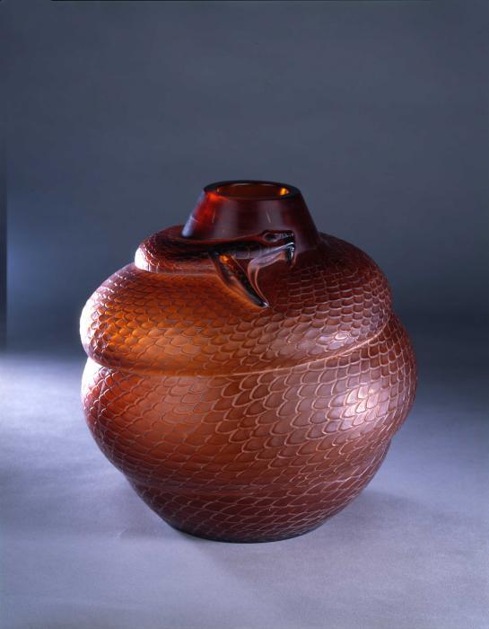 Vase en verre rouge-orangé représentant un serpent, gueule ouverte et crocs déployés, enroulé autour de l'objet comme s'il étouffait une proie.